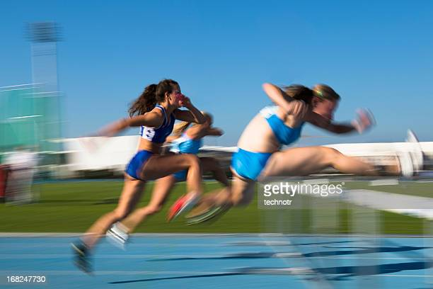 young women at hurdle race 100 m - hurdle stock photos and pictures