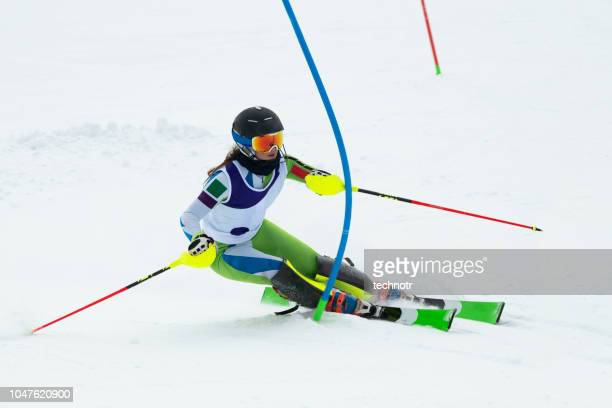 young women at slalom skiing passing the blue gate - female skier stock pictures, royalty-free photos & images