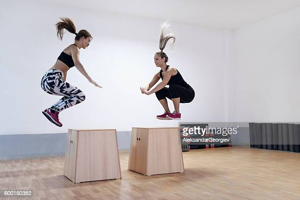 young women athletes doing box jump in the gym - circuit training stock photos and pictures