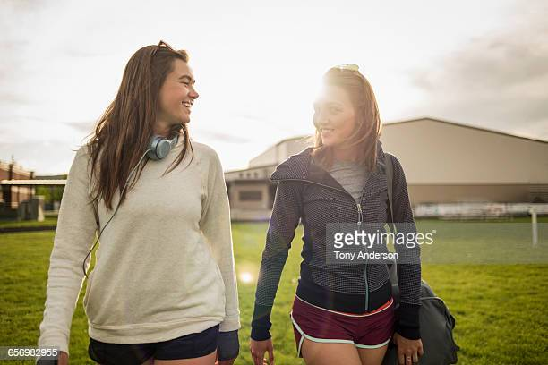 Young women athletes leaving playing field