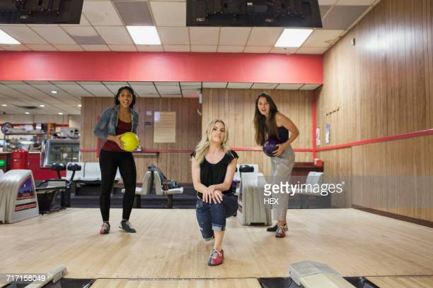 A young women bowling with friends.