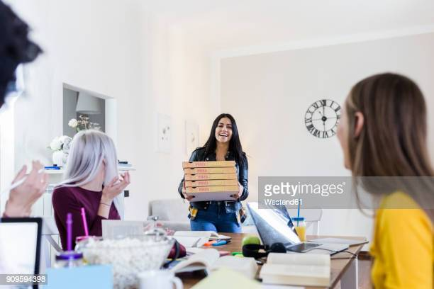 young women bringing pizza for friends studying at home - portare foto e immagini stock