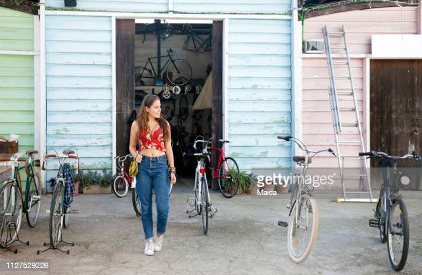 young women buying a bike at flea market - garage sale stock pictures, royalty-free photos & images