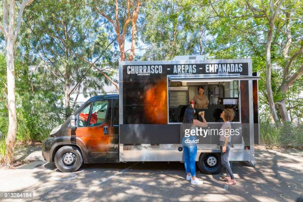 young women buying a meal from food truck - food truck stock pictures, royalty-free photos & images