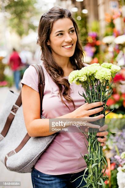 Young women buying flowers at market