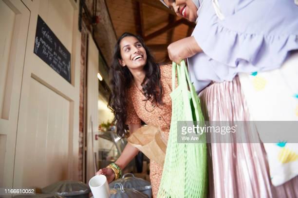young women buying food at plastic free market - zurückhaltende kleidung stock-fotos und bilder