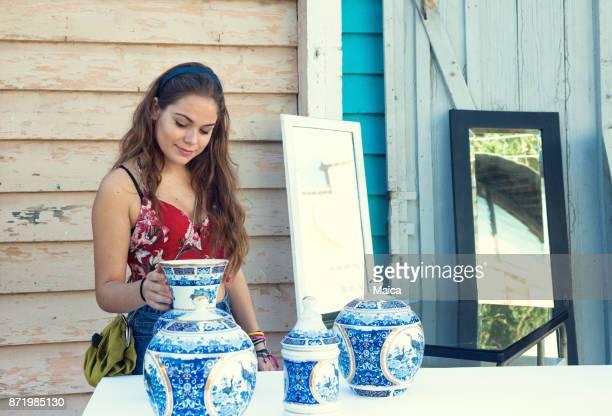 mujeres jóvenes comprar porcelana en el mercado - venta de garaje fotografías e imágenes de stock