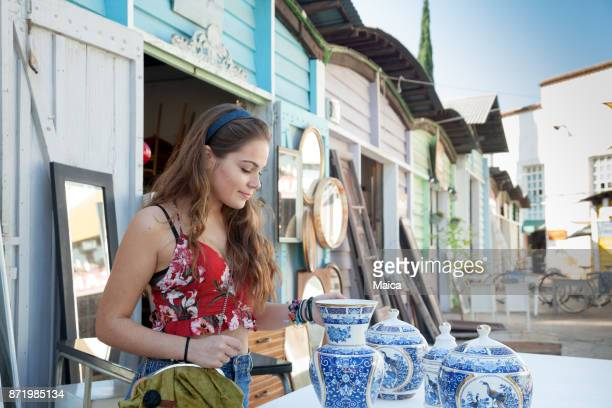 young women buying porcelain at the market - garage sale stock pictures, royalty-free photos & images