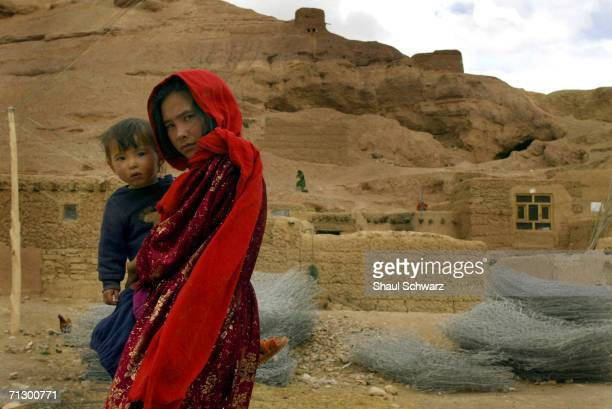 A young women caries a baby as she walks down the street on April 6 2004 in Bamyan Province Afghanistan Almost all of the houses in the city of...