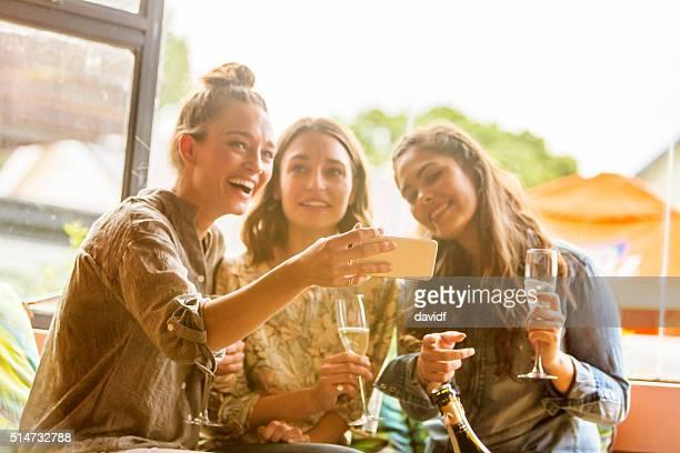 Junge Frauen feiern und Lachen mit einem Telefon und Champagner