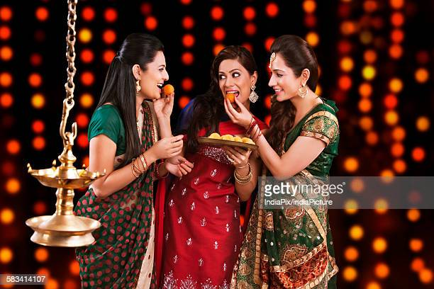 young women celebrating diwali - mithai stock pictures, royalty-free photos & images