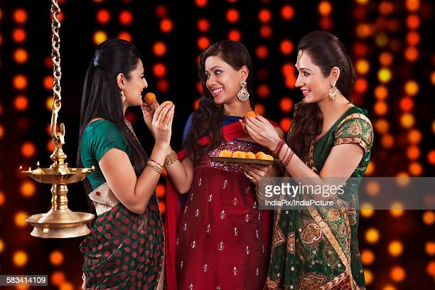 young women celebrating diwali - diwali sweets stock photos and pictures