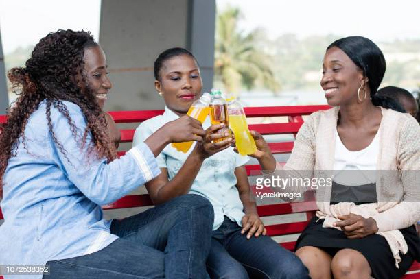 young women celebrating their reunion with beautiful  smiles and drink in their hands. - côte d'ivoire stock pictures, royalty-free photos & images