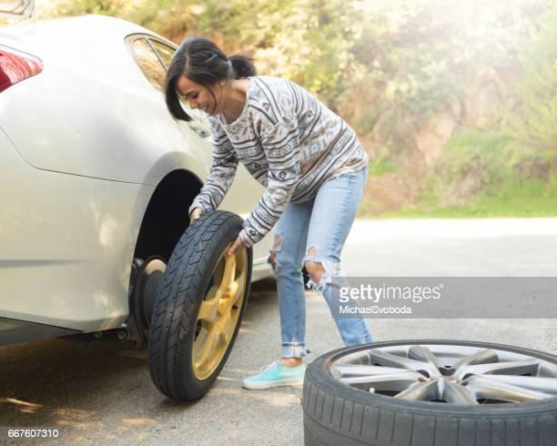 Young Women Changing A Flat Tire