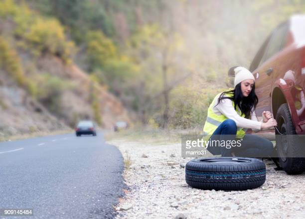 young women changing a flat tire - flat tire stock pictures, royalty-free photos & images
