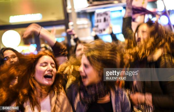 Young women chant slogans as people march down Istiklal Avenue during a feminist night march to mark International Women's Day in Istanbul on March 8...