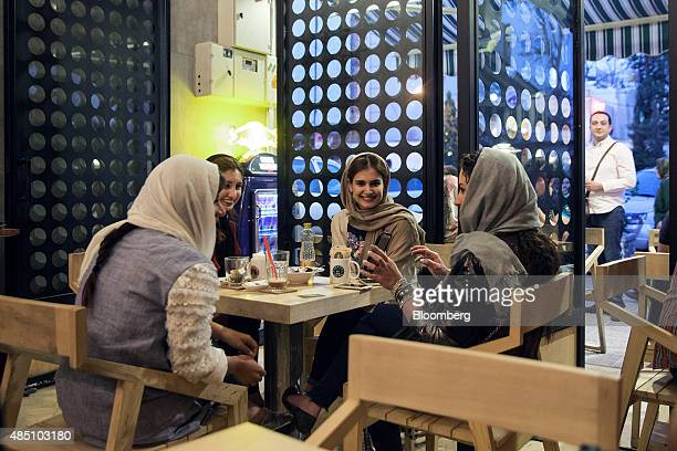 Young women chat and drink coffee at a Raees coffee store in Tehran Iran on Friday Aug 21 2015 Iran plans to raise oil production 'at any cost' to...