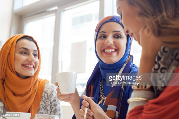 young women chatting at café.  - modest clothing stock pictures, royalty-free photos & images