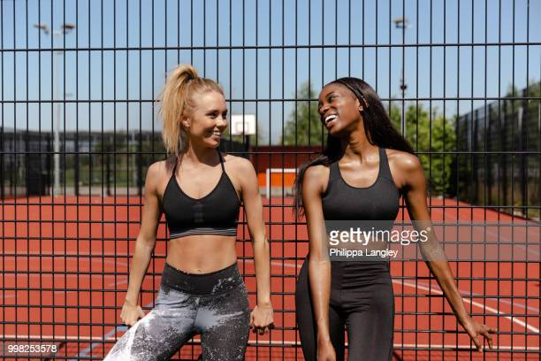 Young women chatting by basketball court
