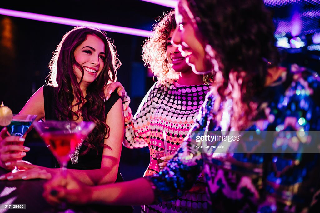 Young women chatting with drinks in a night club : Stock Photo