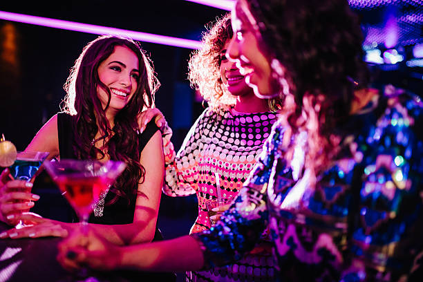young women chatting with drinks in a night club - girls drinking stock pictures, royalty-free photos & images