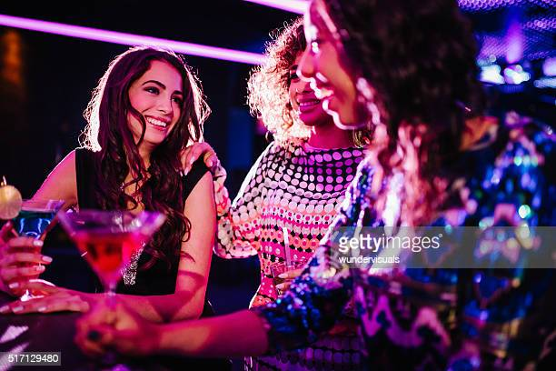 Young women chatting with drinks in a night club
