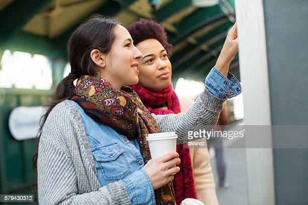Young women checking route map on train platform