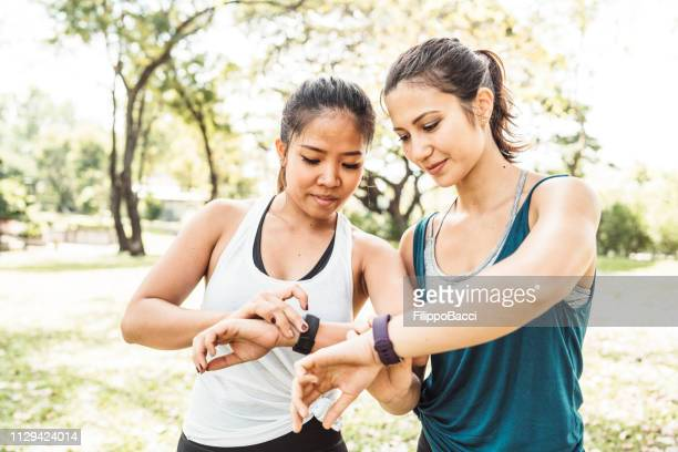 young women checking their fitness trackers at the park - fitness tracker stock pictures, royalty-free photos & images