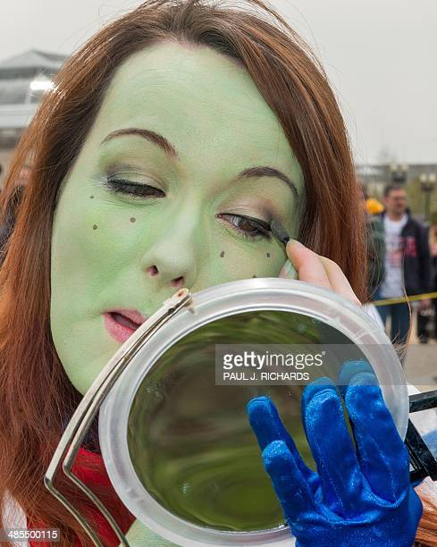 Young women checks her green make-up as she gathers with people dressed in superhero-style costumes at the US Capitol in Washington, DC on April 18...