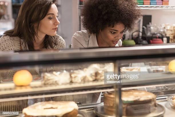Young women choosing cake from cake counter in coffee shop
