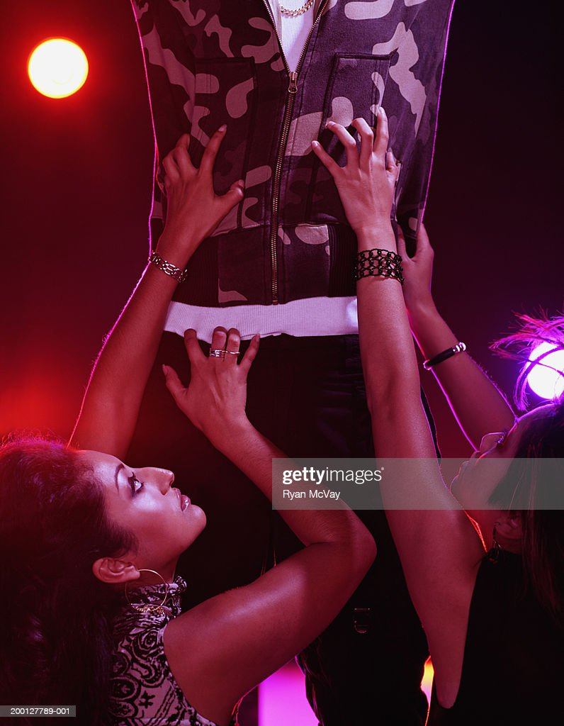 Young women clawing at young man's torso, nightclub : Stock Photo