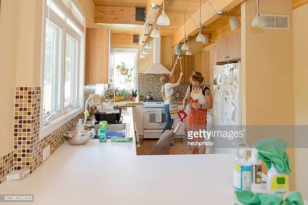 young women cleaning kitchen with green cleaning products - heshphoto stock pictures, royalty-free photos & images