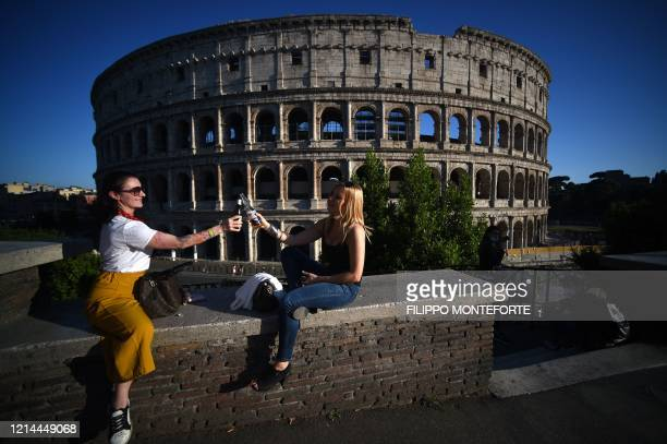 Young women clink bottles of beer as they share an aperitif drink by the Colosseum monument in Rome on May 21 while the country eases its lockdown...