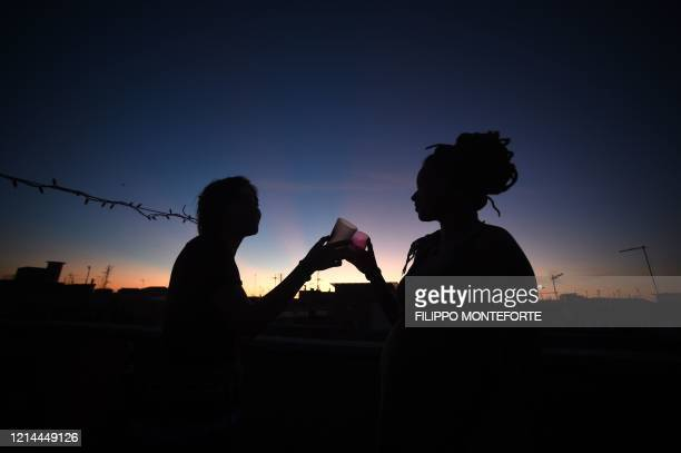 Young women clink glasses during an aperitif drink in Rome on May 21 while the country eases its lockdown after over two months, aimed at curbing the...