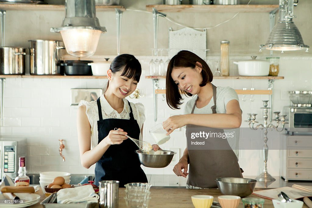Young women cooking together in kitchen : Stock Photo