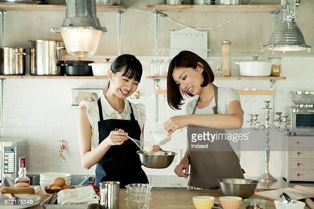 Young women cooking together in kitchen