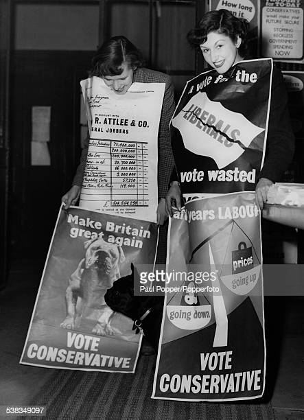 Young women covered with Conservative Party election posters at Abbey House the party headquarters in London in the runup to the General Election...