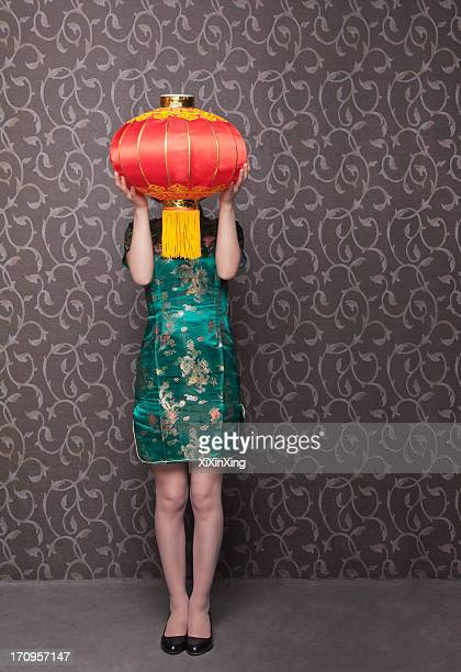 Young women covering her face with a Chinese lantern