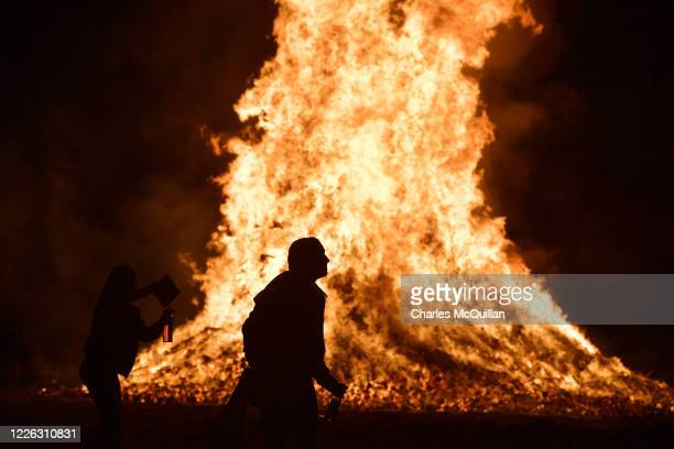 Young women dance in front of the bonfire at the Ballycraigy estate 11th night bonfire on July 11, 2020 in Antrim, Northern Ireland. Loyalists...