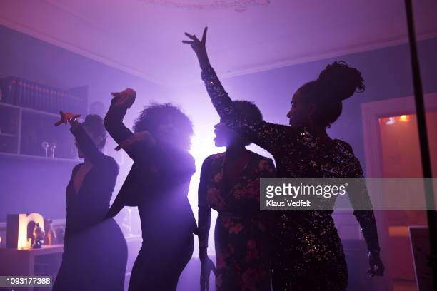 young women dancing and cheering at home party - room after party stock pictures, royalty-free photos & images