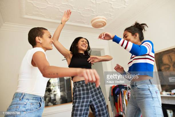 young women dancing and enjoying in bedroom - female friendship stock pictures, royalty-free photos & images