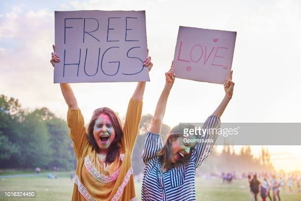 Young women dancing holding up love and free hug signs at Holi Festival