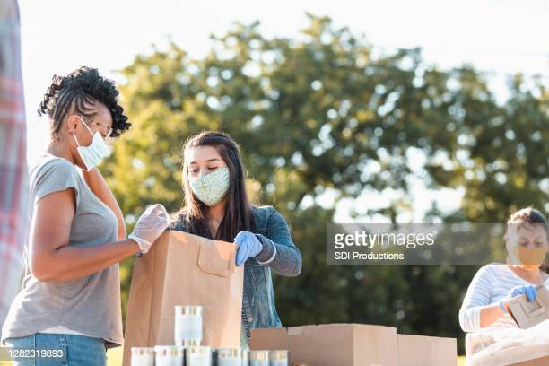 young women discuss contents of bag at food drive - giving stock pictures, royalty-free photos & images