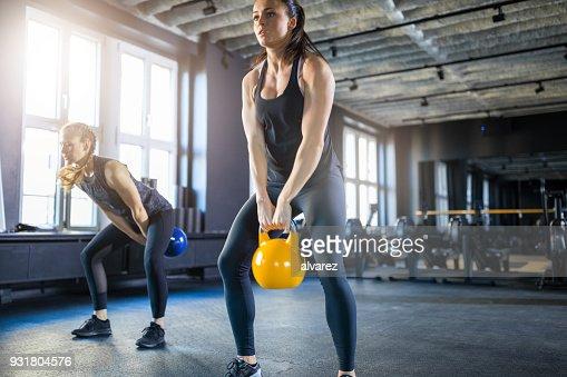 Young women doing kettlebell swings in gym