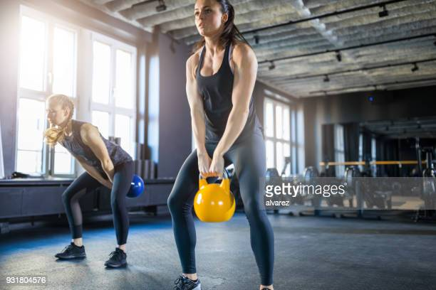Young women doing kettlebell swings in gym