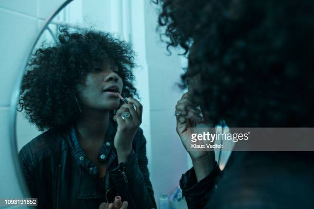 Young women doing make-up in the bathroom mirror at pre-party