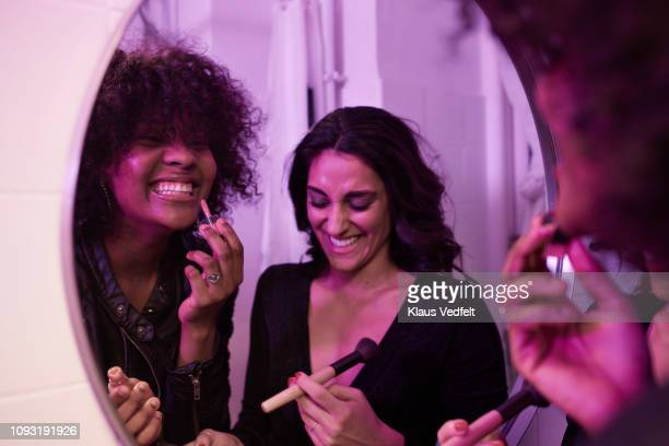 young women doing make-up in the bathroom mirror at pre-party - feriado evento - fotografias e filmes do acervo
