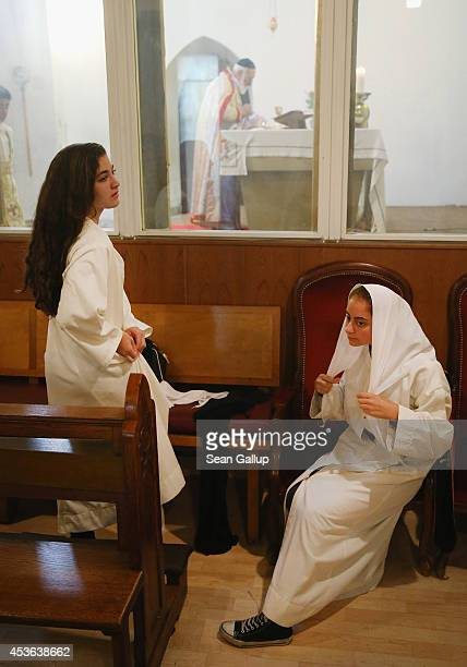 Young women don gowns during Mass at the St Jacob Syrian Orthodox Antioch Church on Assumption Day on August 15 2014 in Berlin Germany In Christian...