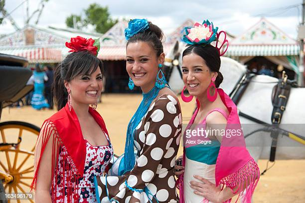 Young women dressed in colourful flamenco dresses at the Seville April Fair or the Feria de abril de Sevilla, Spain