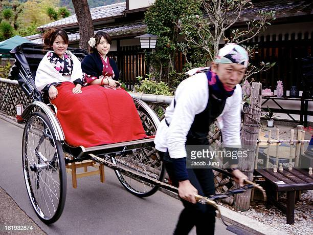 Young women dressed in kimono with a blanket over their laps are pulled along in a rickshaw in Kyoto's scenic Arashiyama district during the height...